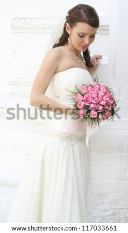 A lovely bride looks down at her bouquet from roses. She is dressed in a simple gown and wearing a veil. - stock photo