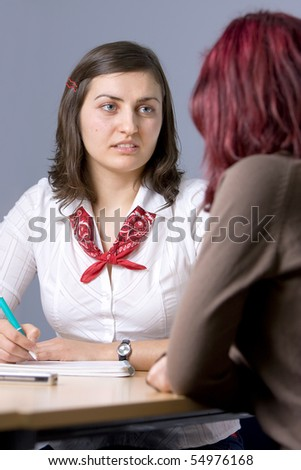 A lovely casual woman taking notes while having an enjoyable discussion with a red haired woman. - stock photo