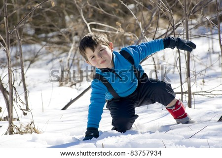 A lovely child playing with the white snow