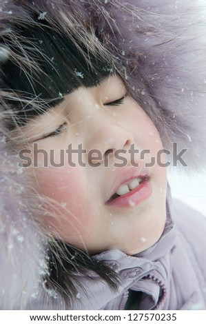 a lovely Chinese girl's face covered with white snow