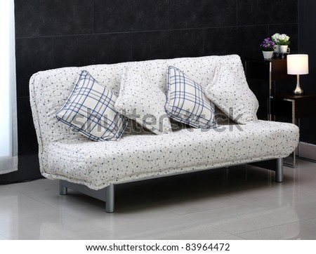 A lovely comfortable sofa bed and cute cushions - stock photo