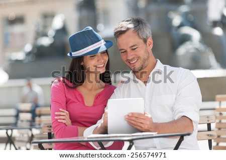 A lovely couple is sitting at an outside bar table, looking at a white tablet. The grey hair man with a beard in a white shirt is holding the tablet. The woman is wearing a blue hat and a pink top. - stock photo