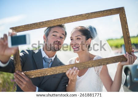 a lovely couple is taking funny selfie for their wedding, taking a frame in front of their faces, behind them a lovely country road - stock photo
