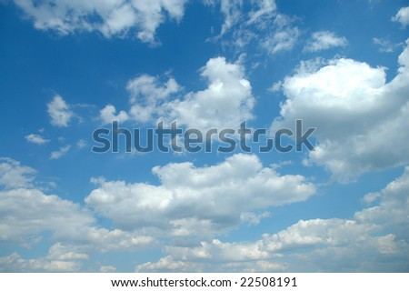 A lovely day with blue sky and light puffy clouds. - stock photo