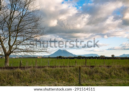 A lovely, early-morning, winter view of Mount Edgecumbe, a volcano in the Bay of Plenty, New Zealand. The grand stretch of farmland and the dramatic sky is a feast for the eyes to bold. - stock photo