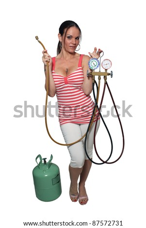 A lovely, exotic, and busty brunette with a set of air conditioning gauges and hoses, and a 30-pound tank of R-22 refrigerant.  Isolated on white background. - stock photo