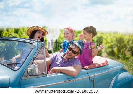 A lovely family is going on vacation in a convertible retro car. they drive on a country road on a sunny day - stock photo