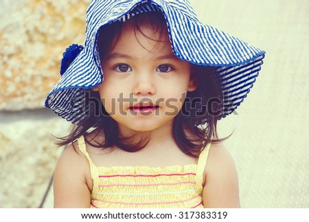 a lovely girl smiling and wearing hat in a vintage color background