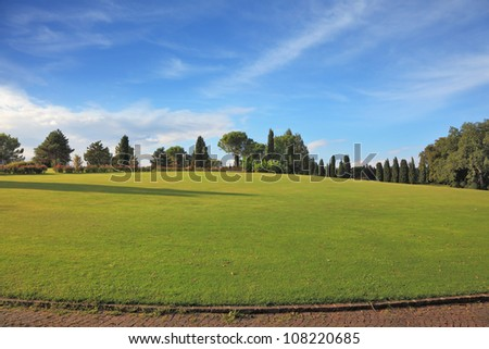 A lovely green lawn grass in the park. Lawn goes around a paved stone path. - stock photo