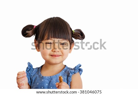 A lovely little girl with piggy tails smiling and eating cookie isolated on white background - stock photo