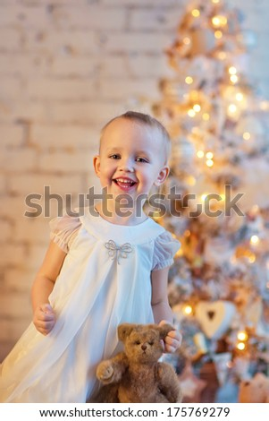 A lovely little 3 year old girl in a beautiful white dress staying in front of the decorated Christmas tree and holding her teddy bear - stock photo