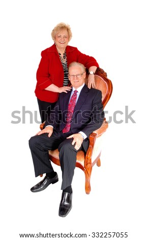 A lovely middle age couple, the man sitting in a armchair and the wife standing behind, formal dressed, isolated for white background.  - stock photo
