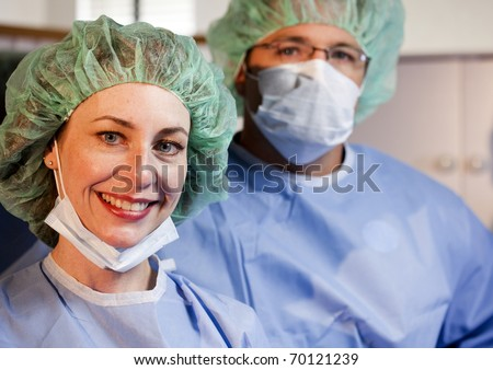 A lovely nurse with her surgical mask pulled away from her face smiles at the camera with an out of focus surgeon in the background.