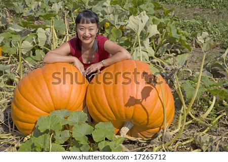 A lovely oriental woman, behind two large pumpkins ready for harvest. - stock photo