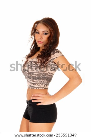 A lovely picture of a young pretty woman standing in black shorts and beige top, serious, isolated on white background.
