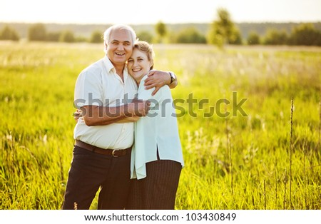 A lovely portrait of a happy senior couple outdoors. - stock photo