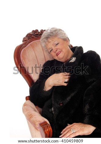 A lovely senior woman in a black fur coat sitting in a pink armchair, 