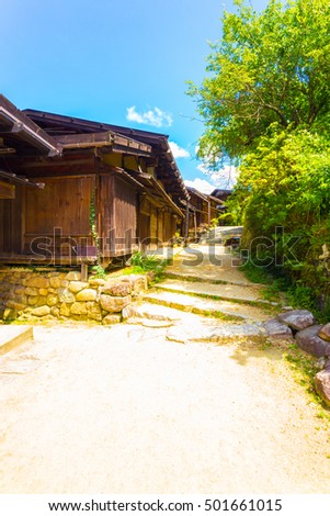 A lovely set of rustic wooden houses and dirt road restored to an ancient countryside feeling on the Nakasendo route in Tsumago village on a sunny day. Vertical