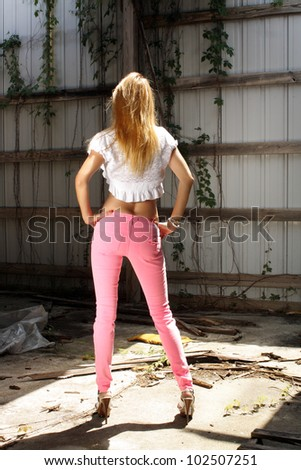 A lovely strawberry-blonde woman stands facing away from the camera wearing pink jeans in a long-abandoned warehouse facility. - stock photo