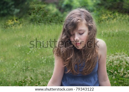 A lovely teen girl sits quietly and downward