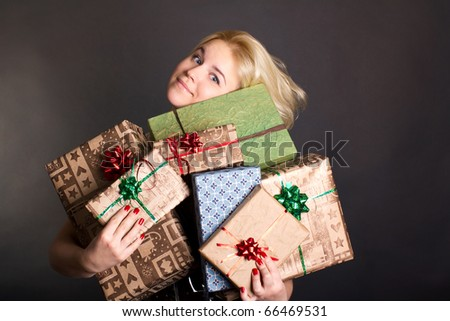 A lovely woman holding a many gift boxes on black background - stock photo