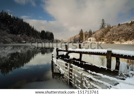 A lovely wooden snow covered jetty by the shores of Loch Ard in Winter at Loch Lomond and the Trossachs National Park, Scotland - stock photo