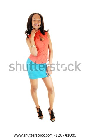 A lovely young and tall black woman standing in the studio for white background in a orange blouse and turquoise skirt.