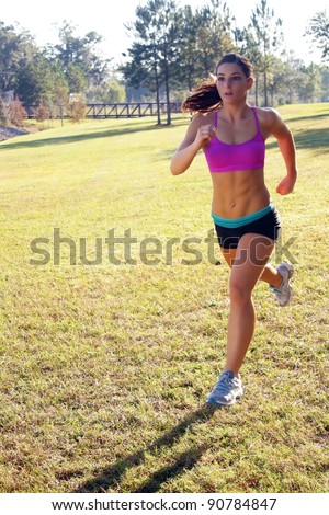 A lovely young athlete with remarkable abdominal musculature jogging outdoors.  Generous copyspace. - stock photo