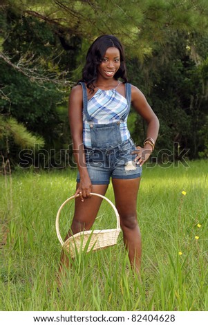 A lovely young black woman stands in a grassy field, holding a woven basket. - stock photo