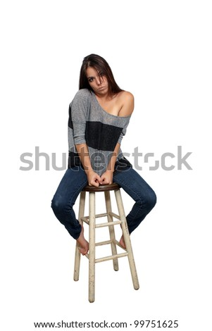A lovely young brunette in casual wardrobe sits on a barstool, isolated on a white background with generous copyspace.