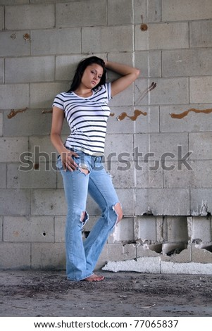 A lovely young brunette wearing tattered jeans and a white T-shirt with black stripes, leans against an old, dilapidated block wall.