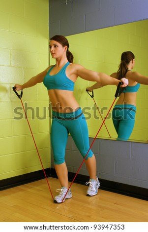 A lovely young brunette with exceptional muscle tone works out with resistance bands in front of a mirror. - stock photo
