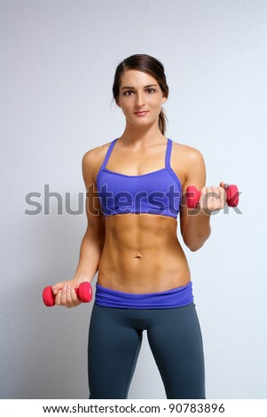 A lovely young brunette with extraordinary abdominal musculature works out with hand weights. - stock photo