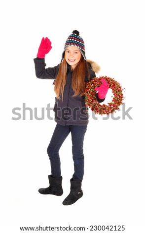 A lovely young girl in a jacket, knitted hat and mittens waiving with her hand and holding an advents wreath, isolated for white background.  - stock photo