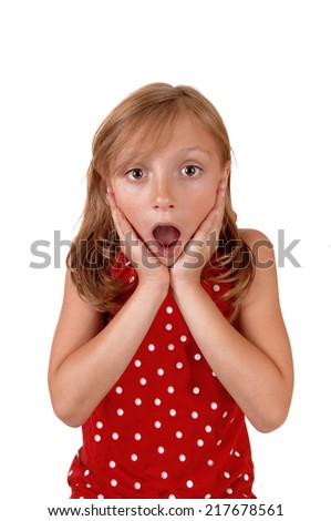 A lovely young girl in a red sweater holding her hands on her face, looking very surprised, isolated for white background.  - stock photo