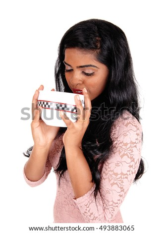 A lovely young Indian woman holding a big bowl to her mouth, with