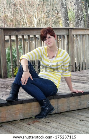 A lovely young redhead sits on a boardwalk. - stock photo