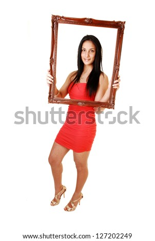 A lovely young teen girl in a red dress and gold high heels, with her long black hair standing in the studio for white background and holding a  picture frame up.