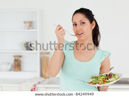A lovely young woman eating salad in her kitchen - stock photo