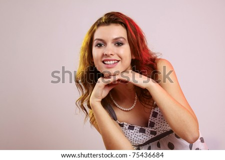 A lovely young woman with hands touching her chin - stock photo