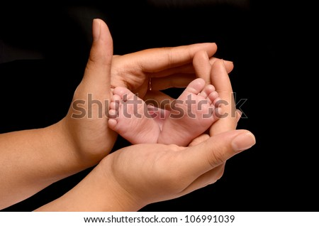 A loving and caring mother is holding the feet of her first new born baby girl and gently enclosing her soft and warm fingers and palms around the tiny little girls feet and toes - stock photo