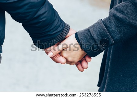 A loving couple holding hands walking in the park .