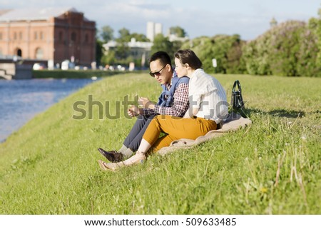A loving couple is sitting on the grass. Portrait of a man and woman are outdoors in St. Petersburg.