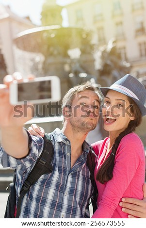 A loving couple is taking a selfie on their phone in the city . The woman is wearing   blue hat. The grey hair man is wearing a black backpack. They are looking at the camera with expressive faces. - stock photo