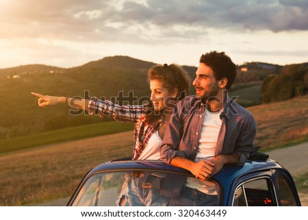 A loving couple, on a summer afternoon, watching sunset from the roof of an old car, around the classical landscape of Tuscany, vineyards and farmland. Woman points to look at a point to her boyfriend - stock photo