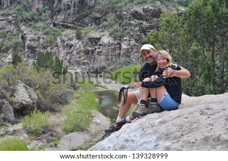 A loving couple sitting on the edge of a high cliff overlooking a creek after catching some trout. - stock photo