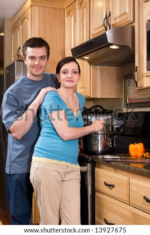A loving couple standing in the kitchen cooking together.  Vertically framed shot with both people looking at the camera. - stock photo