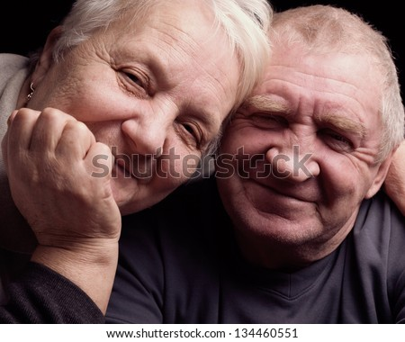 A loving, handsome senior couple on a black background. - stock photo