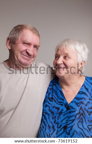 A loving, handsome senior couple on a gray background - stock photo