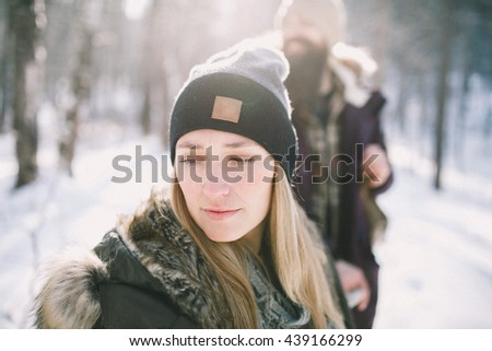 A loving happy young couple walking in the winter woods. Rustic style